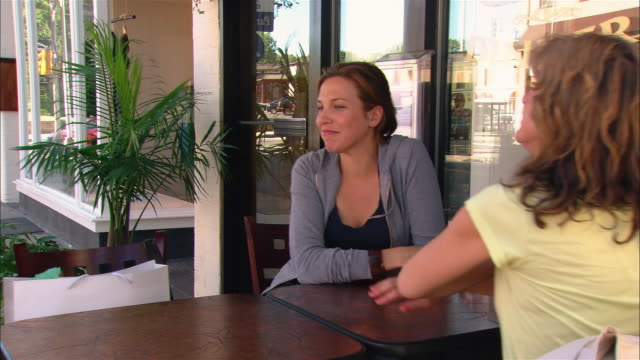 Two women talking at outdoor cafe after placing order with waiter