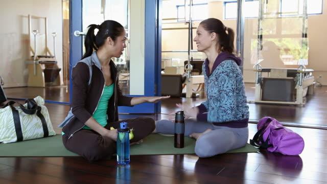 two women talking in gym - auf dem boden sitzen stock-videos und b-roll-filmmaterial