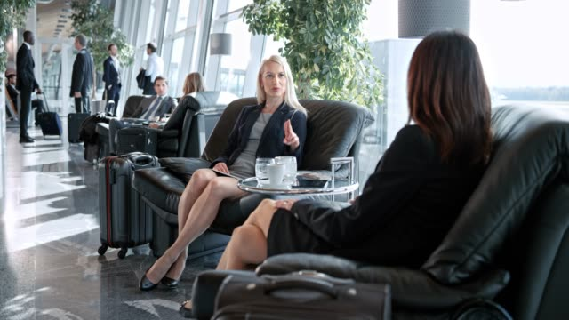 ds two women talking in the business lounge at the airport - sala d'imbarco video stock e b–roll