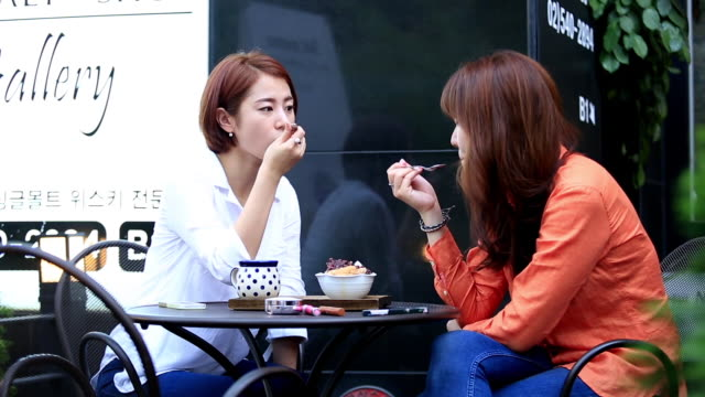 Two women talking to each other while eating ice dessert at café