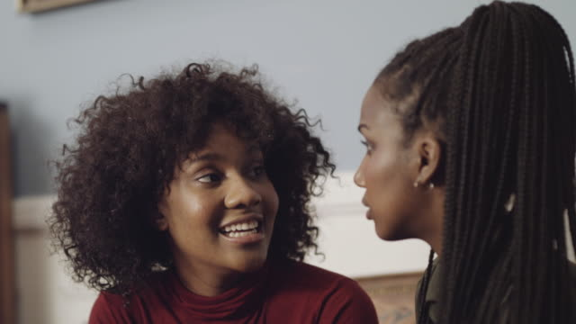 vidéos et rushes de two women talking together in sofa - coiffure afro