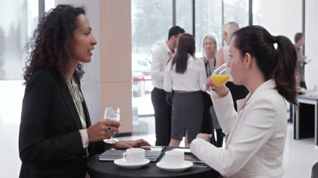 two women talking while drinking coffee in the lobby of a conference hall - 10 seconds or greater stock videos & royalty-free footage