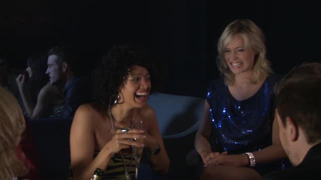 MS Two women talking with friends in bar / London, UK