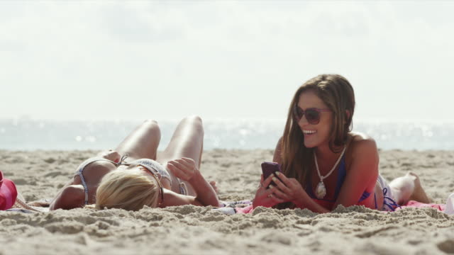ws two women text messaging on beach / south beach, miami, florida, usa - sdraiato video stock e b–roll