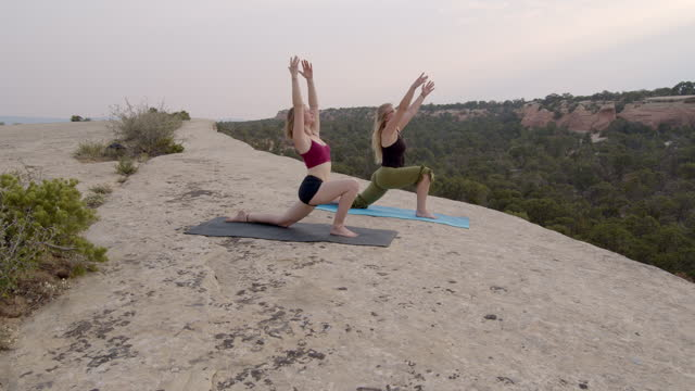 stockvideo's en b-roll-footage met two women transitioning from downward dog to crescent lunge yoga pose in the hills near fruita colorado at sunset - in kleermakerszit
