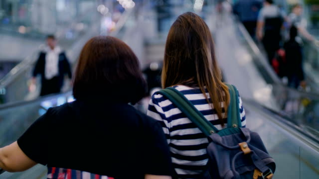 two women traveler on moving walkway in airport - only mid adult women stock videos and b-roll footage