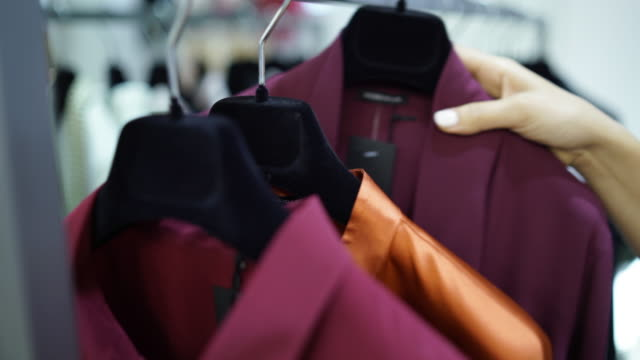 two women trying on business jackets in a store - giacca video stock e b–roll