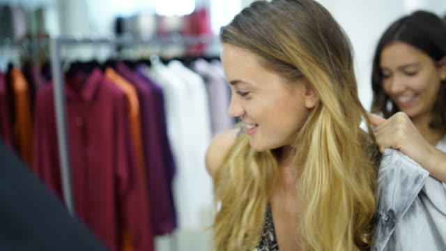 two women trying on clothing in a store - anpassen stock-videos und b-roll-filmmaterial