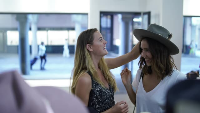 vídeos de stock e filmes b-roll de two women trying on hats in a clothing store - mercadoria