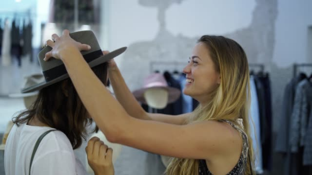 two women trying on hats in a clothing store - cappello video stock e b–roll