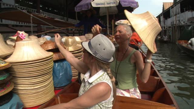 MS PAN Two women trying on hats on Damnoen Saduak floating market, Bangkok, Thailand