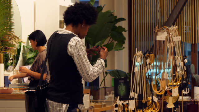 stockvideo's en b-roll-footage met ms two women trying on jewelry while shopping in boutique - plank meubels