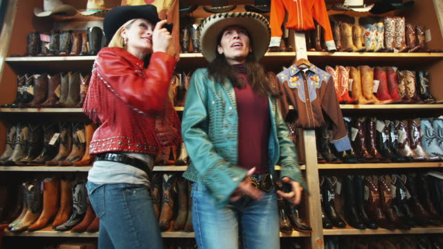two women trying on leather jackets and cowboy hats at a western store
