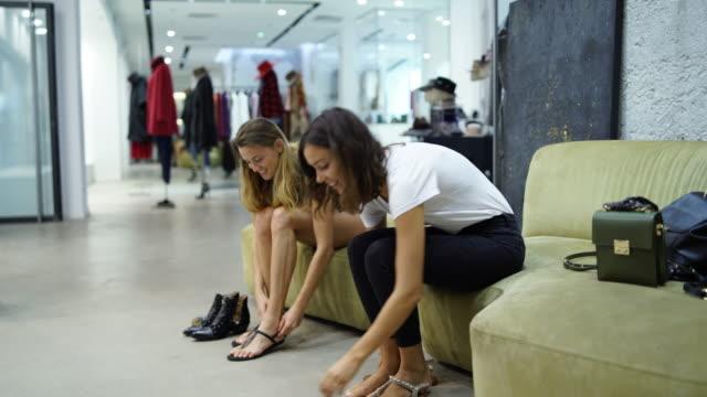 stockvideo's en b-roll-footage met twee vrouwen die proberen op schoenen in een kledingwinkel - moving past