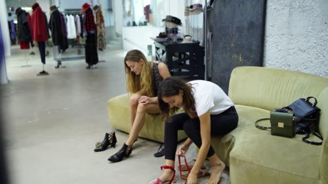 Zwei Frauen, die versuchen auf Schuhe in einem Bekleidungsgeschäft