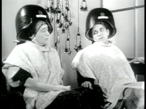 stockvideo's en b-roll-footage met two women under hair dryers in beauty parlor hair salon woman saying sot not to repeat this but sister's son left last week for norway other woman... - 1943