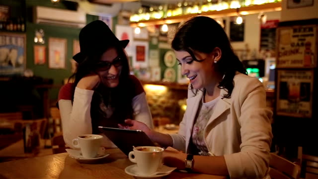two women using digital tablet  in a coffee shop - stationary stock videos & royalty-free footage