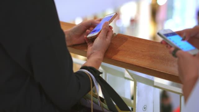 vídeos de stock, filmes e b-roll de duas mulheres usando o smartphone em shopping center - loja de produtos eletrônicos