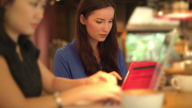 Two women, using technology in a cafe.