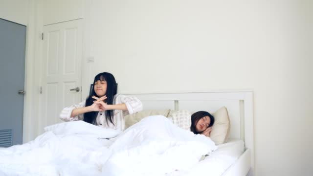 2人の女性が遅く目を覚ます - 寝室点の映像素材/bロール