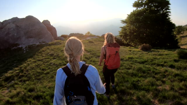 two women walk along mountain ridgetop at sunrise - tracking shot stock videos & royalty-free footage