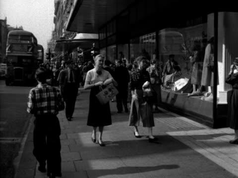 Two women walk along Oxford Street 1956