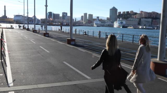 two women walk along waterfront corridor, talking - porto marittimo video stock e b–roll