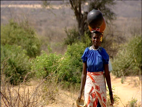 two women walk carrying large water gourds on their heads dodoma region tanzania - tanzania stock videos & royalty-free footage