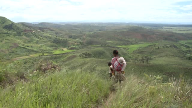 stockvideo's en b-roll-footage met two women walk down a grassy hill in madagascar. available in hd. - heuvel