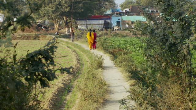 Two women walk down dirt path in bright colored saris.