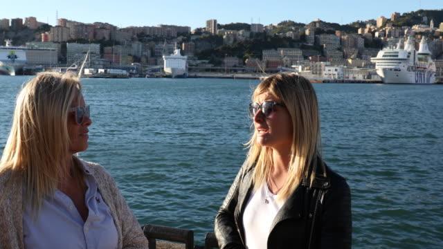 vídeos y material grabado en eventos de stock de dos mujeres a pie relajarse frente a costanera, hablando - puerto