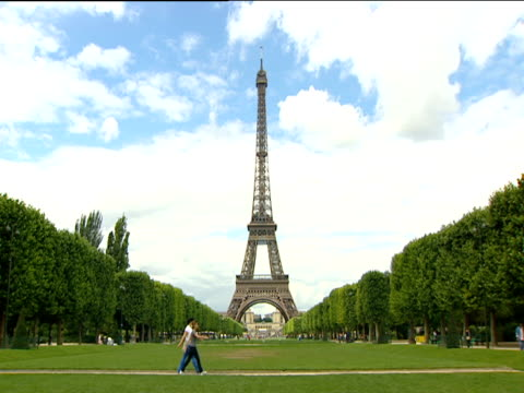 Two women walk through Parc du Champs de Mars Eiffel Tower in background Paris