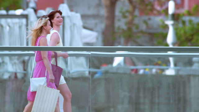 SLO MO Two women walking across a bridge