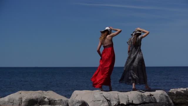 two women walking across rocks at beach - shadow stock videos & royalty-free footage