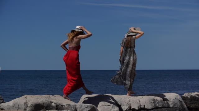 Two women walking across rocks at beach