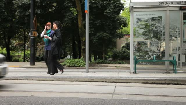ws pan two women walking and talking after leaving streetcar / portland, oregon, usa - portland oregon点の映像素材/bロール