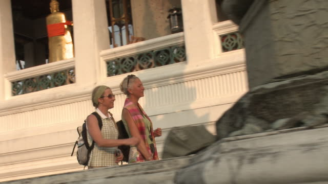MS PAN Two women walking at Wat Phra Kaew (Temple of the Emerald Buddha), Bangkok, Thailand