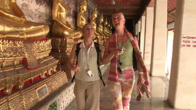 MS TD DS Two women walking at Wat Phra Kaew (Temple of the Emerald Buddha), Bangkok, Thailand