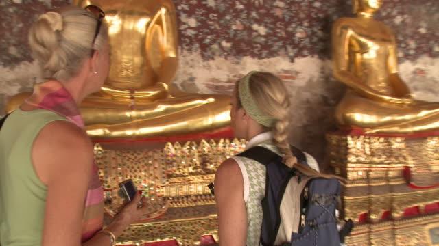 WS DS. MS Two women walking at Wat Phra Kaew (Temple of the Emerald Buddha), Bangkok, Thailand