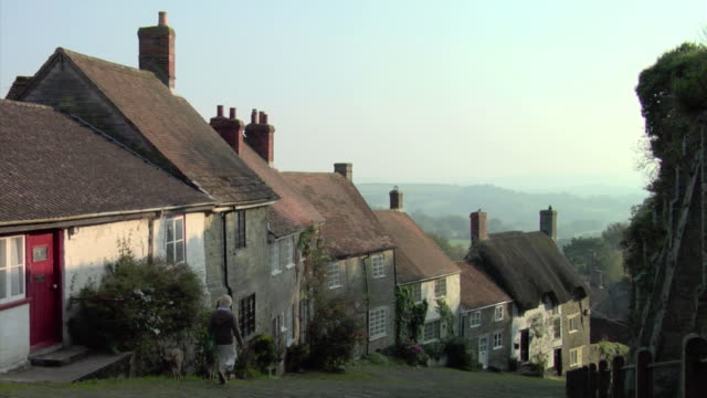 WS Two women walking dogs down Gold Hill past cottages / Shaftesbury, England