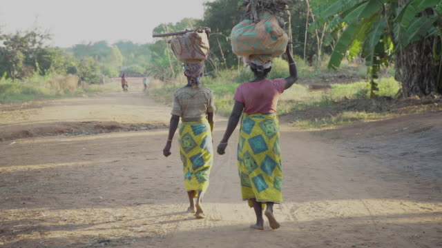 two women walking down dirt road in african village - village stock videos & royalty-free footage
