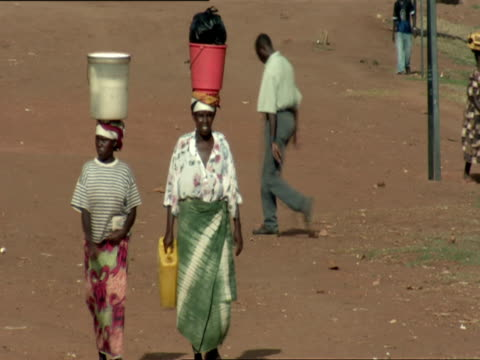 MS PAN Two women walking down dirt road while balancing buckets on their heads / Nyamirambo, Kigali, Rwanda