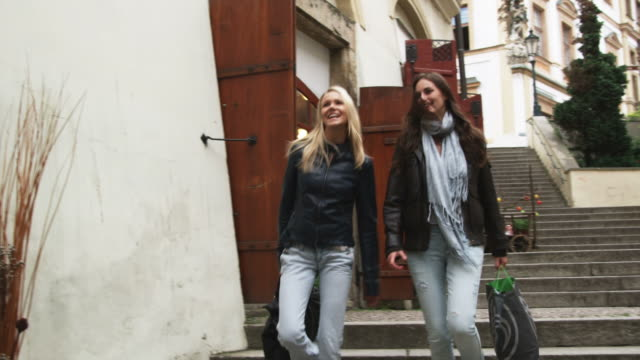 stockvideo's en b-roll-footage met two women walking down the stairs on a city street - praag