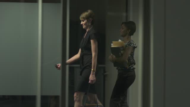 ms pan two women walking in office corridor, chicago, illinois, usa - side view stock videos & royalty-free footage