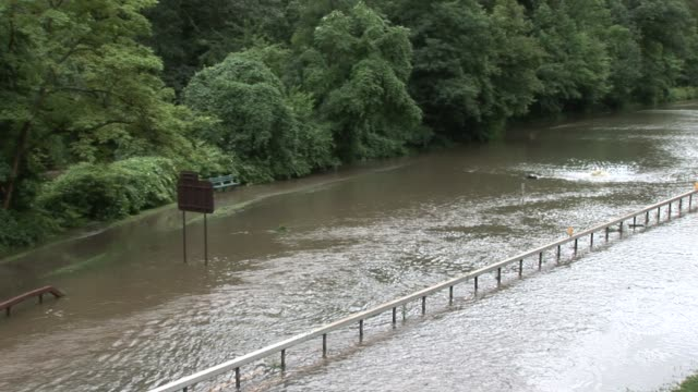 two women walking near flooded bronx river parkway. pan right to reveal flooded parkway bronx river parkway flooded on august 28, 2011 in scarsdale,... - hurricane irene stock videos & royalty-free footage
