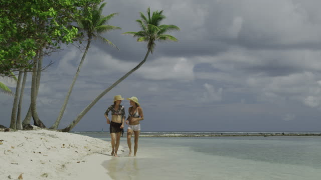 two women walking on the beach - isola di tahaa video stock e b–roll