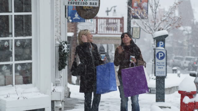 two women walking out of a shop onto a snowy street - park city utah video stock e b–roll
