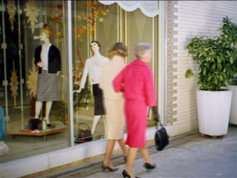 1962 two women walking stop to look in display window of clothing store / third woman passes