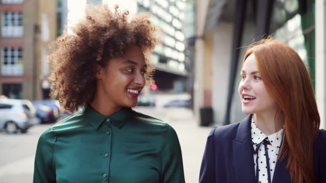 vidéos et rushes de ts - two women walking, talking and smiling - coiffure afro