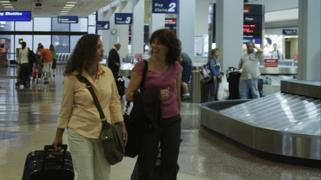 Two women walking the airport at baggage claim.